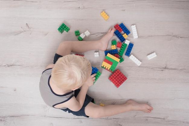 Menino loiro está construindo colorido. vista do topo