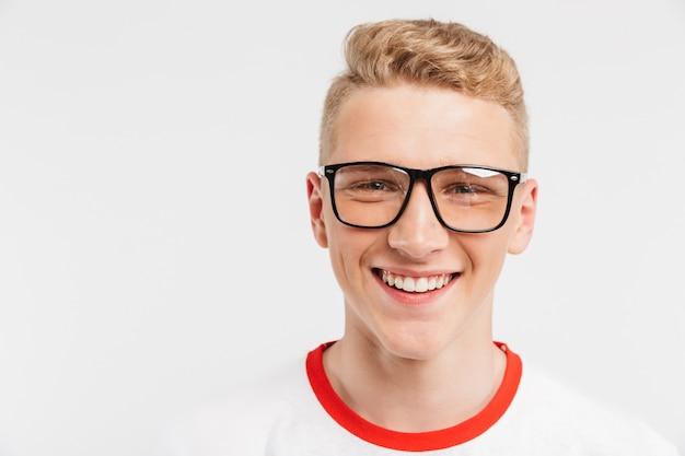 Menino loiro estudante tendo pele saudável limpa usando óculos sorrindo com dentes brancos, isolados no branco