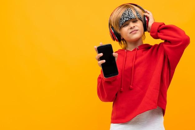 Menino loiro europeu com um capuz vermelho ouve música em fones de ouvido vermelhos e mantém o smartphone em amarelo