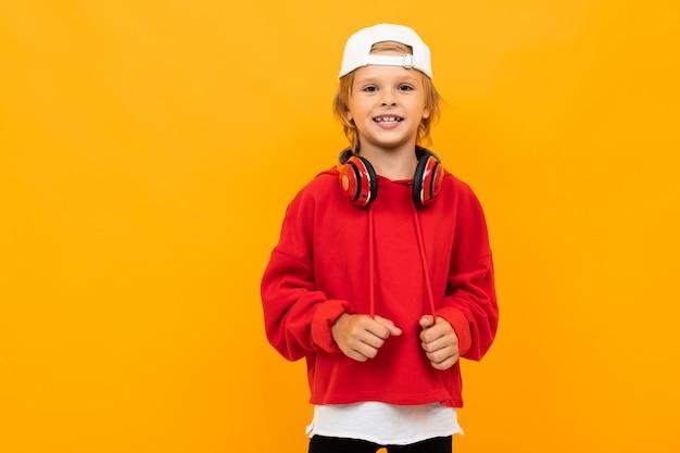 Menino loiro europeu em um capuz vermelho com fones de ouvido vermelhos com um boné de beisebol branco na laranja