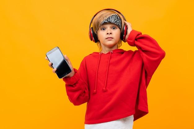 Menino loiro europeu em um capuz vermelho ouve música em fones de ouvido vermelhos e mantém o smartphone com maquete em laranja