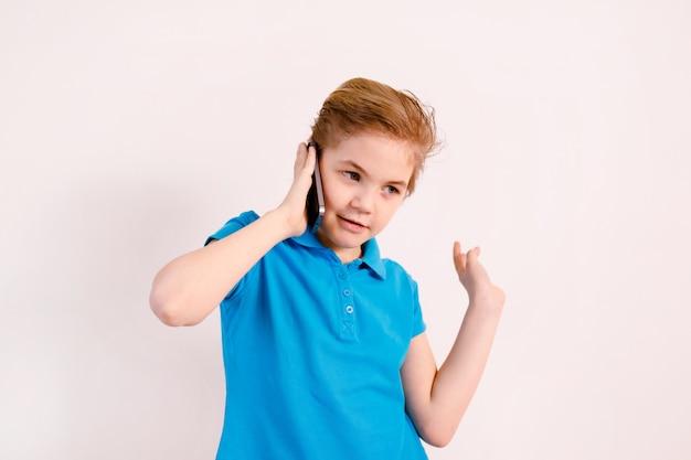 Menino loiro falando ao telefone