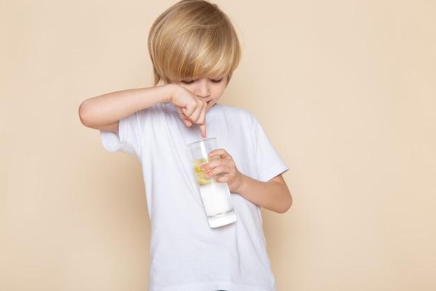 Menino loiro fofo adorável em camiseta branca, segurando o copo com a bebida de água na mesa-de-rosa