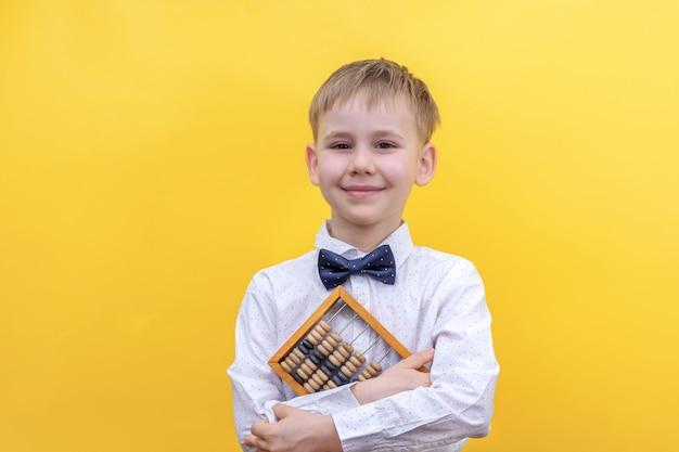 Menino loiro fofo com uma camisa segurando um ábaco de madeira