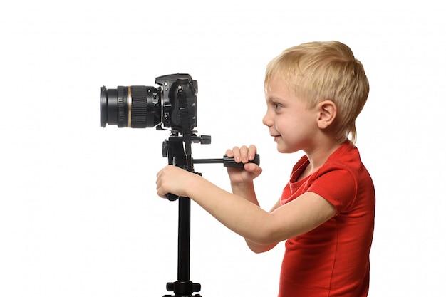 Menino loiro grava vídeo na câmera dslr