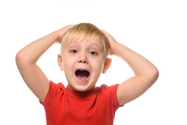 Menino loiro gritando em uma camiseta vermelha cruzou os braços atrás da cabeça
