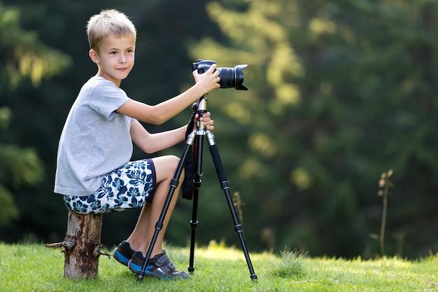 Menino loiro jovem criança sentada no tronco de árvore na clareira gramada tirando foto com a câmera do tripé.