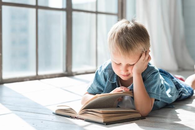Menino loiro lendo livro perto da janela à luz do sol