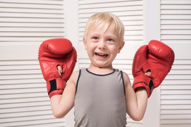Menino loiro lindo em luvas de boxe vermelhas. conceito de esportes