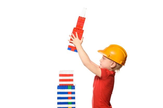Menino loiro no capacete de construção e camiseta vermelha constrói um arranha-céu a partir dos detalhes do designer. isolar na parede branca. vista lateral.