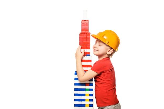 Menino loiro no capacete de construção e uma camisa vermelha fica e abraços torre construída a partir de designer de peças.