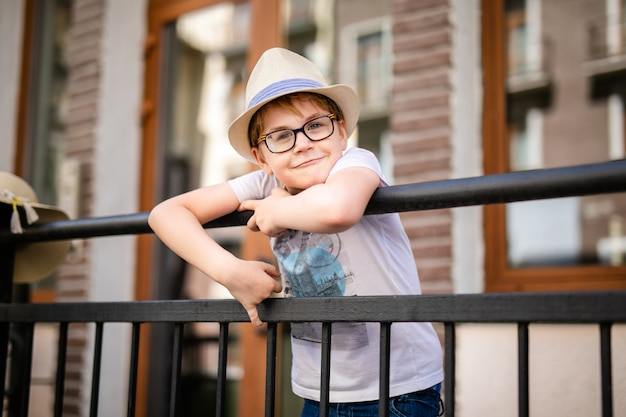 Menino loiro no chapéu de palha e óculos grandes ficar entre belas casas antigas