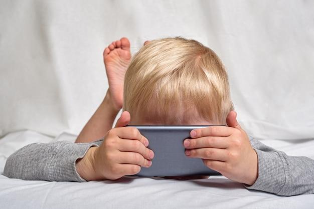 Menino loiro olhando algo que seu nariz enterrado em um smartphone, deitado na cama. gadget leisure