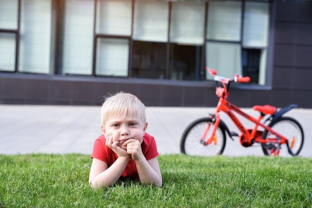Menino loiro pensativo descansando no gramado