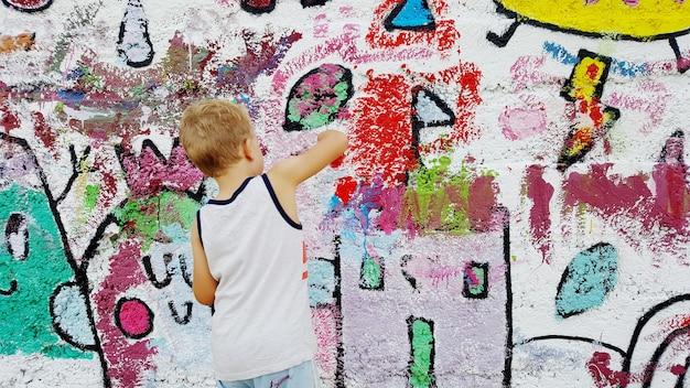 Menino loiro pintando um mural na parede da escola com escovas