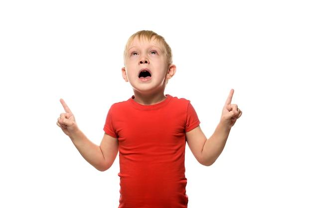 Menino loiro que espirra em uma camiseta vermelha está de pé e apontando com os dedos indicadores para cima, sobre fundo branco.