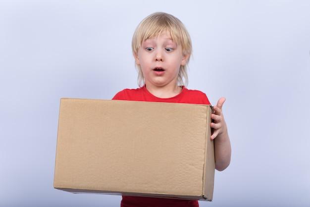 Menino loiro, segurando a caixa grande e pensando. criança surpresa com caixa em mãos no espaço em branco