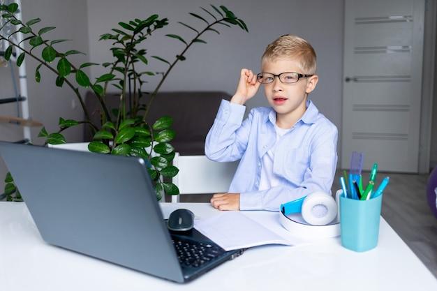 Menino loiro sorridente de óculos faz uma videochamada via laptop durante o ensino à distância em casa