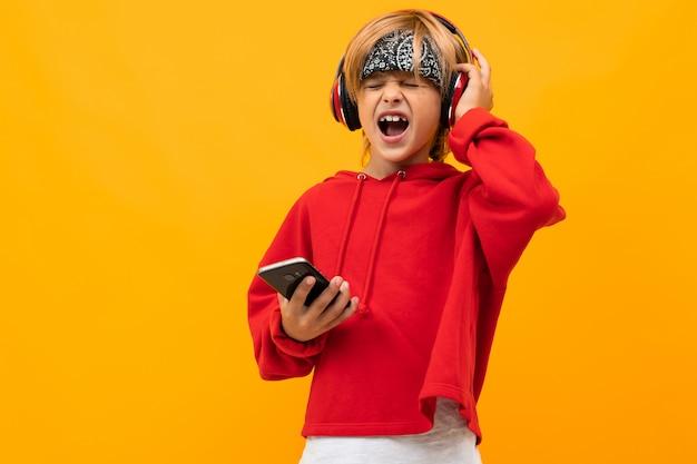 Menino loiro sorridente europeu em um capuz vermelho concentre-se em ouvir música em fones de ouvido vermelhos e mantém o smartphone em amarelo