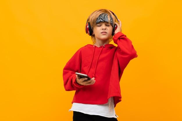 Menino loiro sorridente europeu em um capuz vermelho concentre-se em ouvir música em fones de ouvido vermelhos e mantém o smartphone em laranja