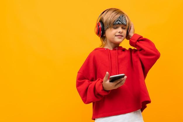 Menino loiro sorridente europeu em um capuz vermelho concentre-se em ouvir música em fones de ouvido vermelhos e mantém o smartphone na parede amarela