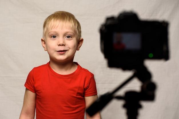 Menino loiro sorridente na frente da lente da câmera. pequeno blogueiro de vídeo. estúdio em casa