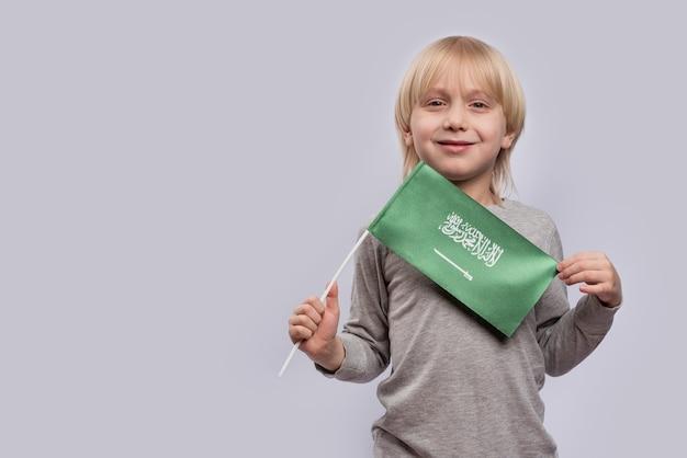 Menino loiro sorridente segurando a bandeira da arábia saudita. viajar para a arábia saudita com crianças.