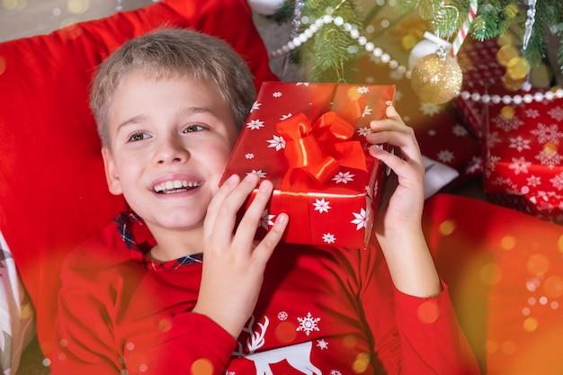 Menino loiro sorridente segurando uma caixa de presente festiva e deitado no chão perto da árvore de natal