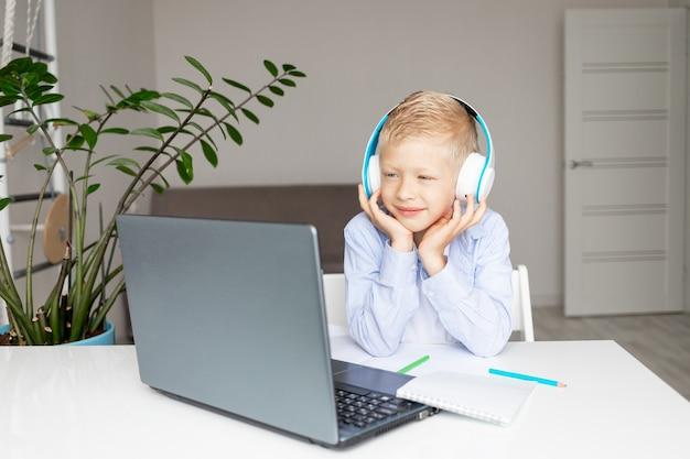 Menino loiro sorridente usando fones de ouvido faz uma videochamada via laptop durante o ensino à distância eletrônico em casa, conceito de volta às aulas