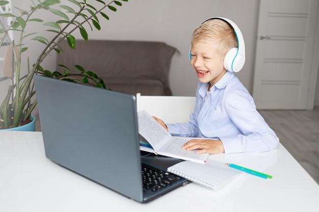 Menino loiro sorridente usando fones de ouvido faz uma videochamada via laptop durante o ensino à distância em casa