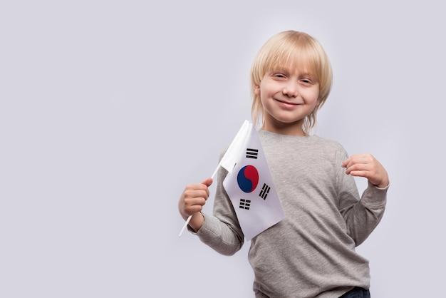 Menino loiro sorrindo e segurando bandeira da coreia do sul