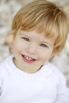 Menino loiro sorrindo em um rolling stones