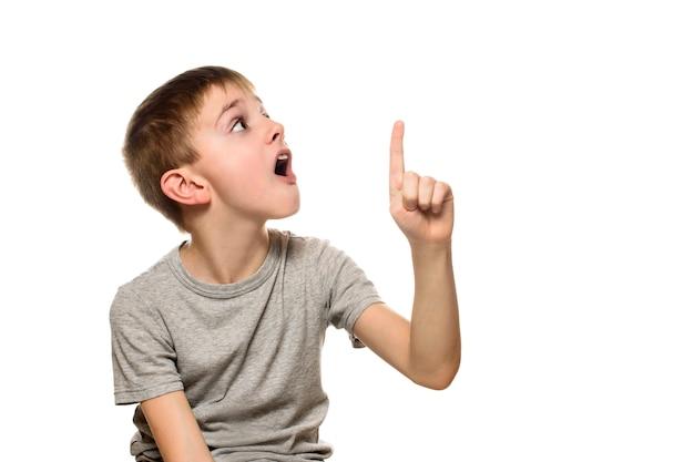 Menino loiro surpreso em uma camiseta cinza fica e aponta com os dedos indicadores para cima