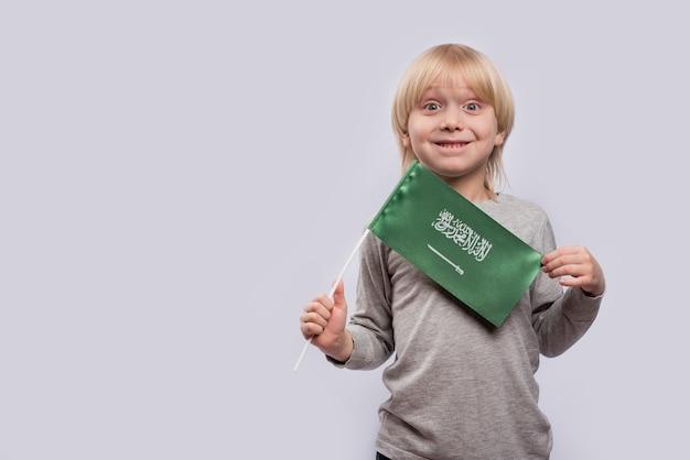 Menino loiro surpreso, segurando a bandeira da arábia saudita. viajar para a arábia saudita com crianças.