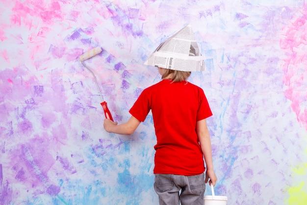 Menino loiro vista traseira em camiseta vermelha e calça jeans cinza, pintando paredes coloridas