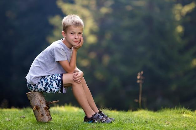 Menino louro bonito novo da criança que senta-se no coto de árvore no esclarecimento gramíneo verde no dia de verão brilhante.