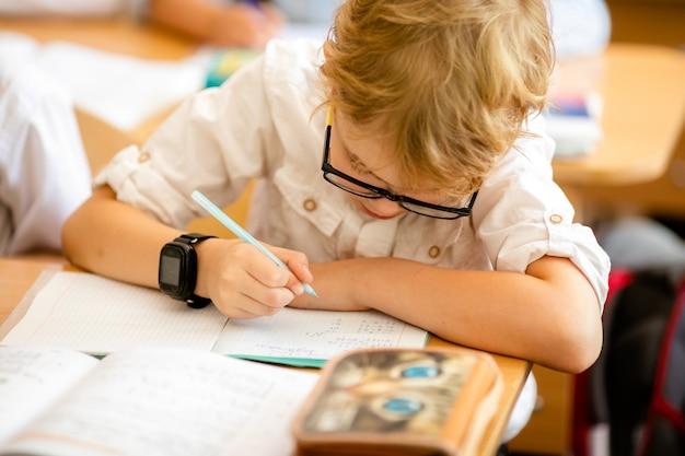 Menino louro com os vidros pretos grandes que sentam-se na sala de aula, studing, sorrindo. educação na escola primária, primeiro dia na escola