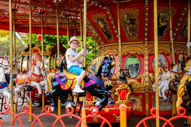 Menino louro no chapéu de palha e em vidros grandes que montam o cavalo colorido no carrossel do carrossel.