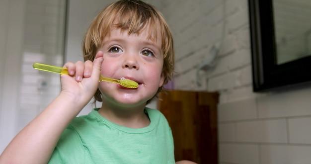 Menino louro pequeno que aprende escovando seus dentes no banho doméstico.