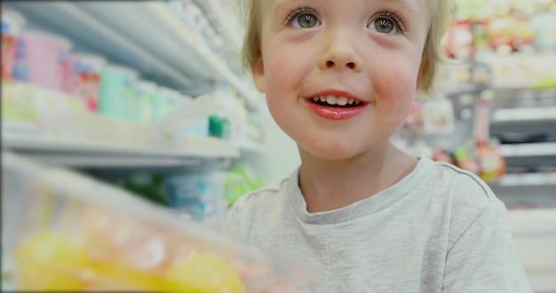 Menino louro pequeno que compra no supermarke. a criança escolhe produtos lácteos na geladeira