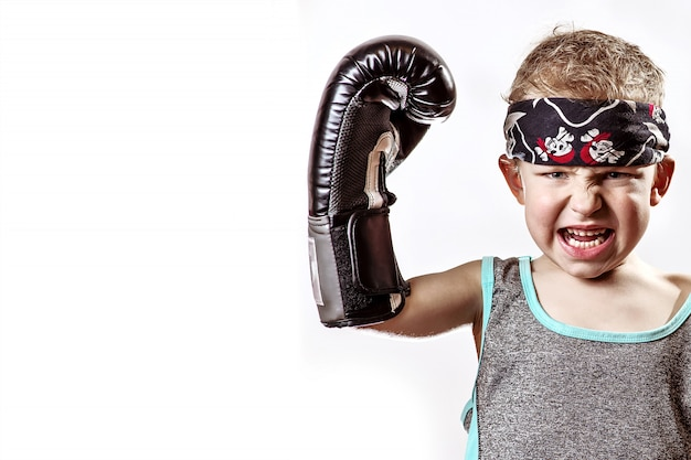 Menino lutando em luvas de boxe e bandana na luz