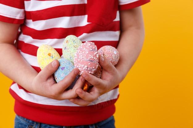 Menino mãos segurando um monte de ovos de páscoa coloridos