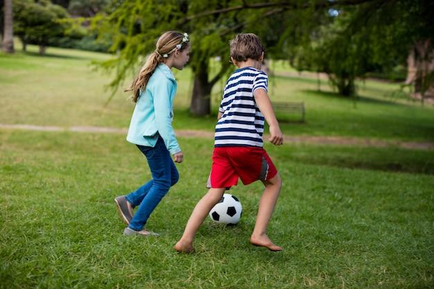 Menino menina, jogando futebol