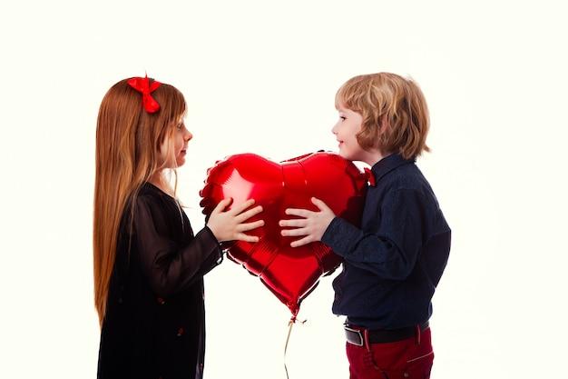 Menino menina, ligado, um, fundo branco, segurando, um, balloon, coração vermelho