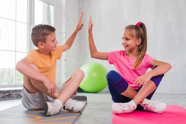 Menino menina, sentando, ligado, esteira exercício, dar, alto cinco