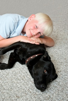 Menino, mentindo topo, cão, sorrindo, retrato