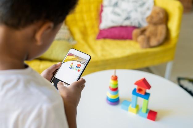Menino mestiço contemporâneo segurando um smartphone na mesa com seus brinquedos enquanto tira uma foto da composição no jardim de infância