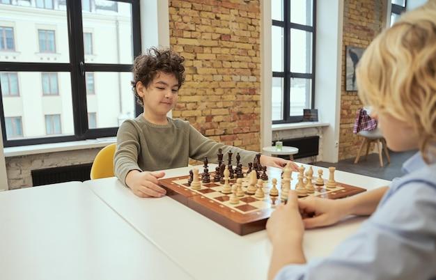 Menino motivado sentado na sala de aula e planejando uma jogada enquanto joga xadrez no