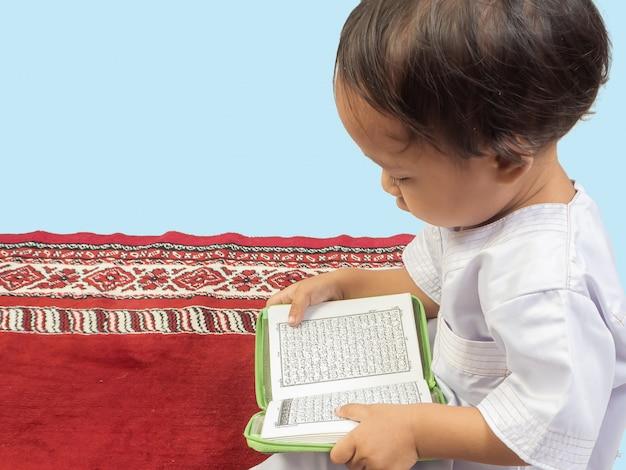 Menino muçulmano em um vestido lendo o alcorão