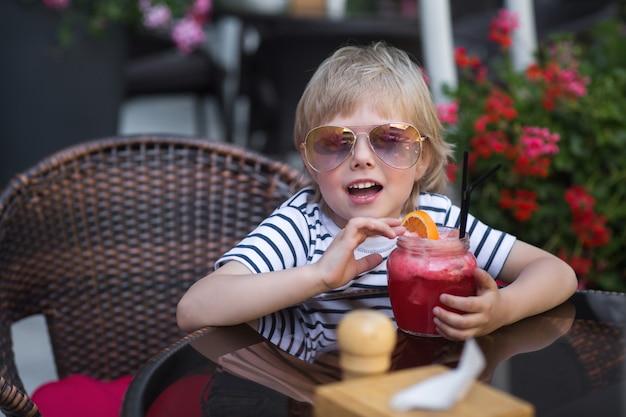 Menino muito bonitinho no café bebendo limonada.